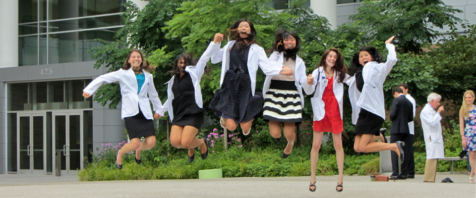 Medical students jump in the air in Hope Plaza, a green space on campus.