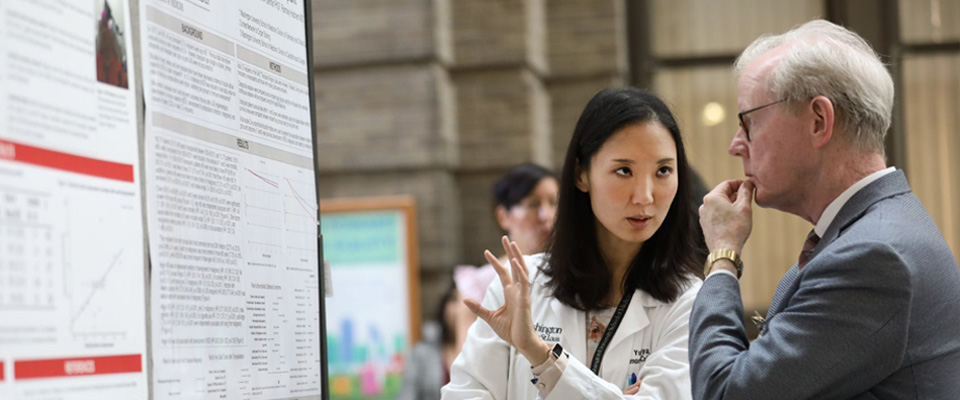 A medical student talks to a faculty member in front of a poster depicting the student's research project.